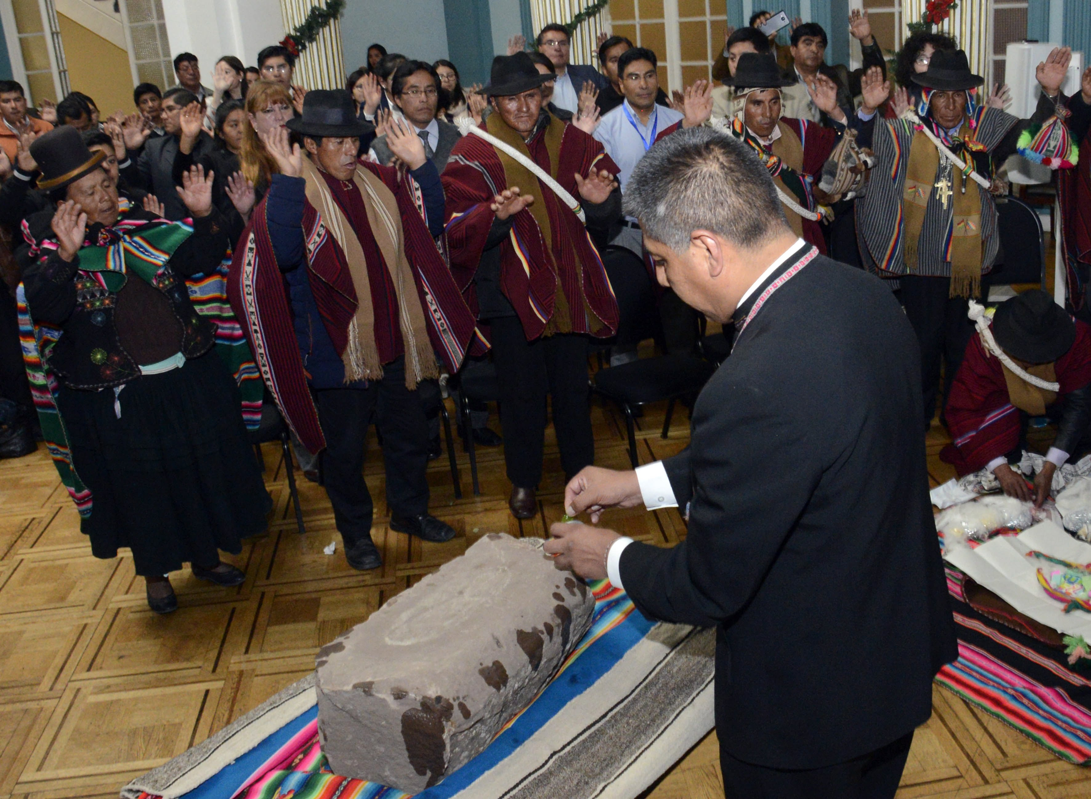 Photo made available by the Bolivian Information Agency (ABI) shows Bolivian Foreign Minister, Fernando Huanacuni (R), participating in the delivery of the world's oldest human footprint set in stone to the Bolivian Sullkatiti community in La Paz, Bolivia, Dec. 29, 2017.