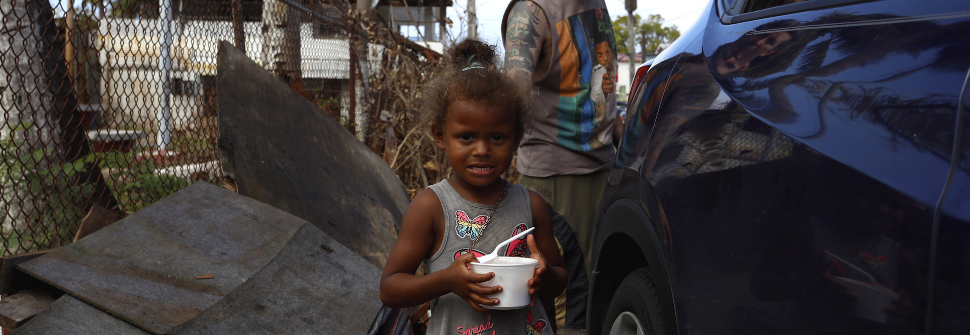 "Juan Carlos Jimenez, volunteer of the ""Plato Caliente"" project, observes the girl Isaura García after bringing her plate of food on October 6, 2017, in Barrio Obrero of Santurce district in San Juan, Puerto Rico."