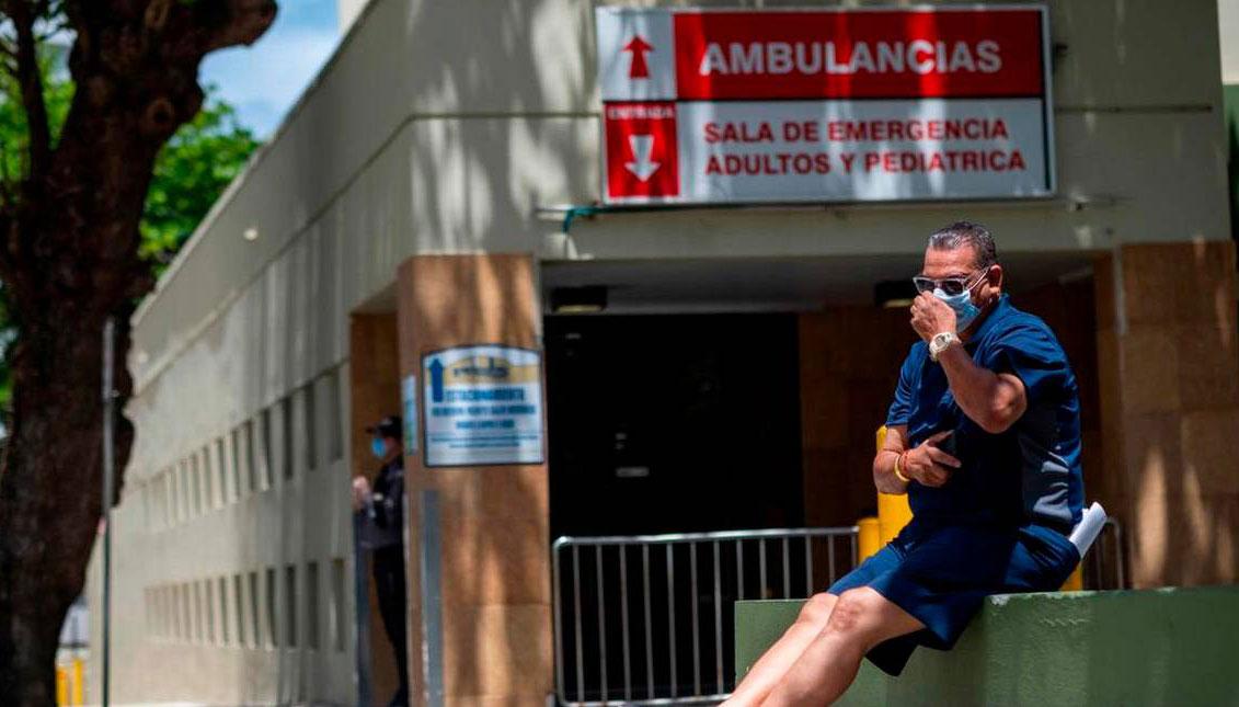 Un hombre con una máscara quirúrgica se sienta frente a la entrada de la sala de emergencias del Hospital Comunitario Presbiteriano de Ashford en San Juan, Puerto Rico, donde el primer paciente con coronavirus de la isla murió ese mismo día, el 21 de marz