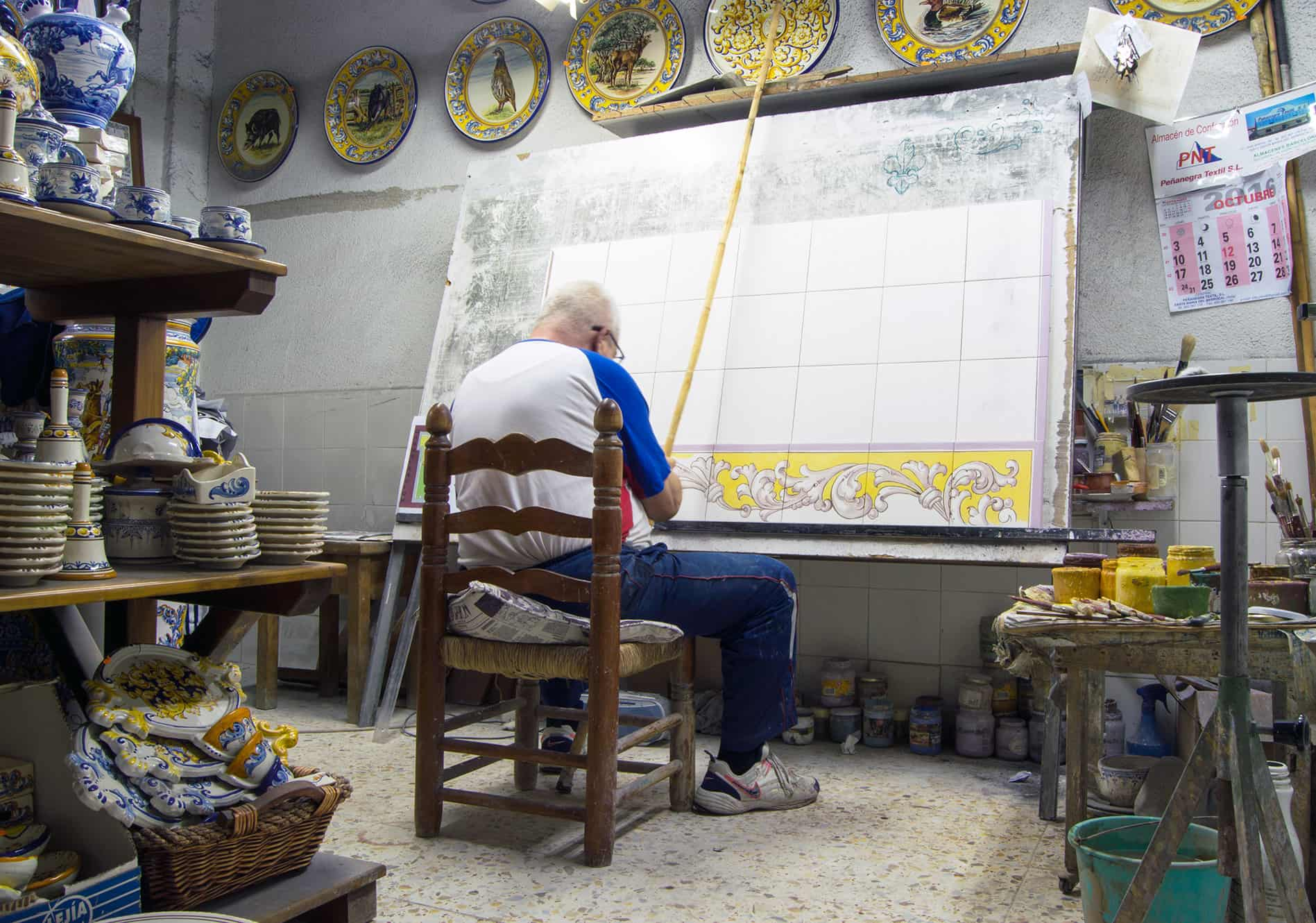 Ceramic painter working on tiles in his workshop in Talavera de la Reina