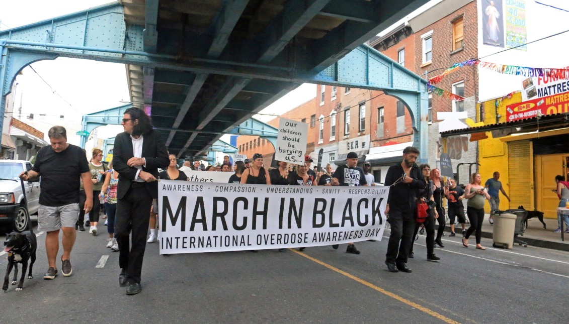 """Jose de Marco of ACT UP Philadelphia and Dan Martino hold the """"March In Black"""" as they lead the march down Kensington avenue towards Huntington station."""