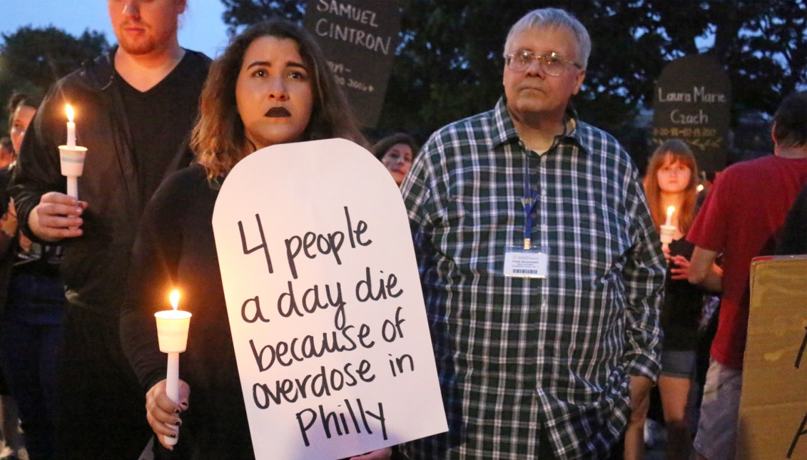 """A woman holds a candle during the vigil at McPherson Square. Her signs read """"4 people a day die because of an overdose in Philly."""""""