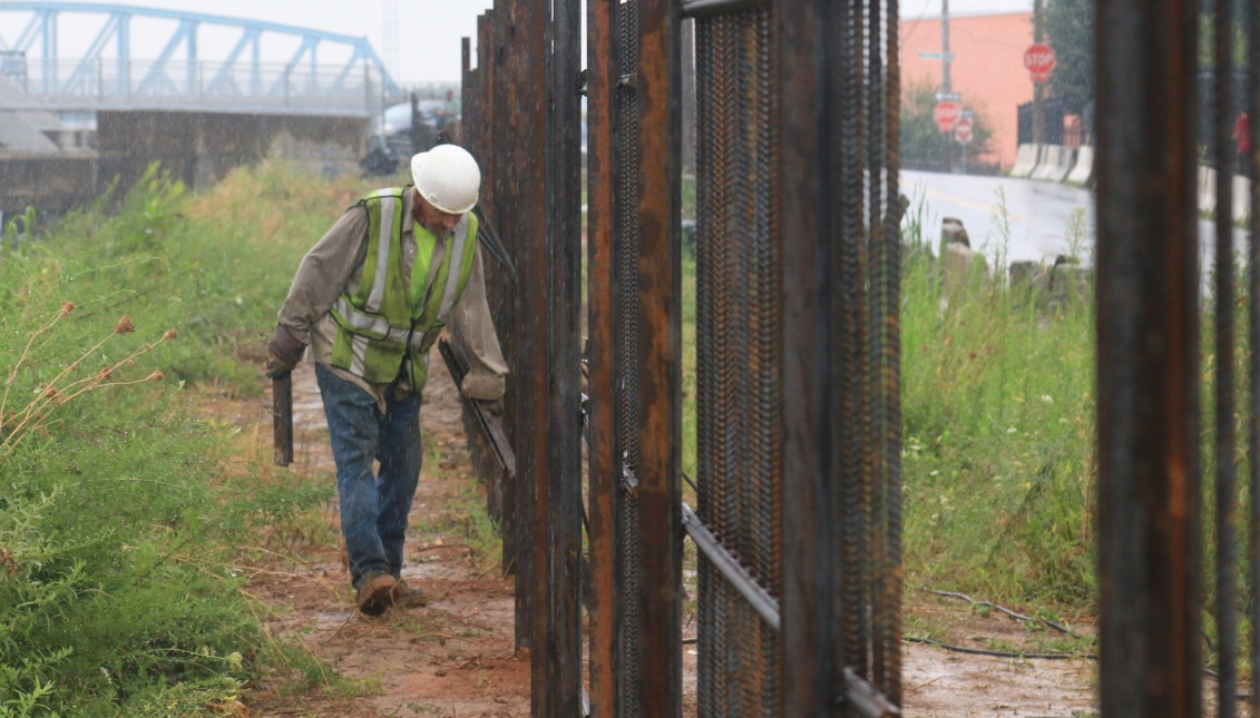 "A Conrail worker examines the previously installed parts of the rebar fence. Although it is a strong fence, one worker commented saying ""If they want it, they'll find a way."" Photo: Matthew Haubenstein"