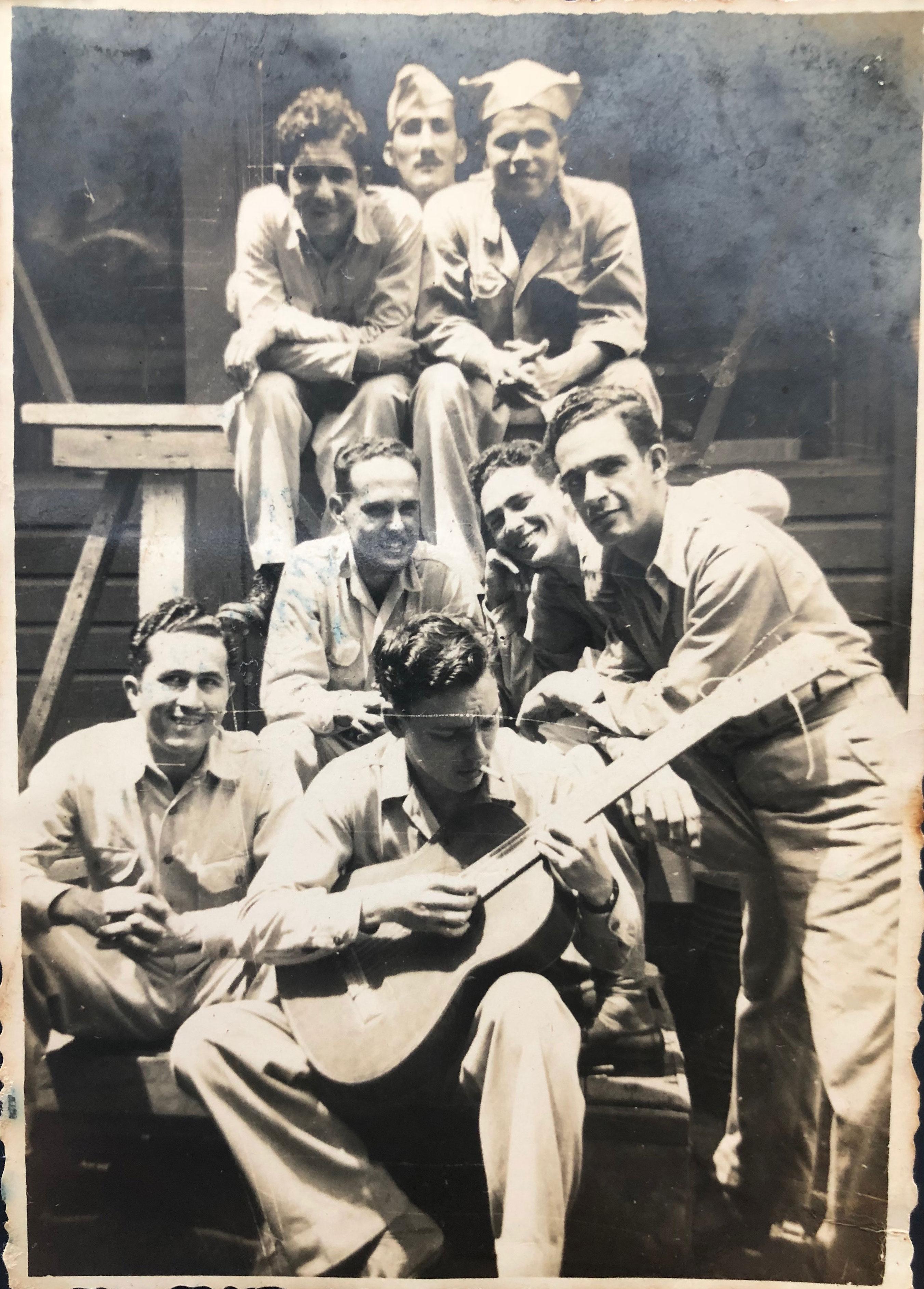 Eloy Estrada, abajo con la guitarra, junto a compañeros puertorriqueños en la Segunda Guerra Mundial. Foto: Cortesía Familia Estrada.
