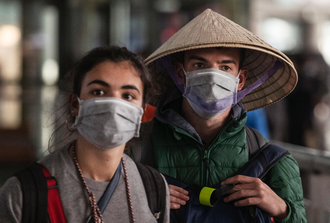 Foreign tourists walk in the arrivals area at Beijing Capital Airport on January 30, 2020 in Beijing, China. (Photo by Kevin Frayer/Getty Images)
