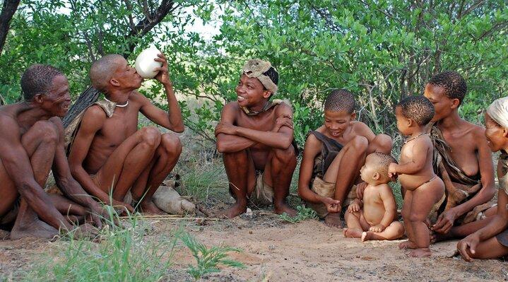 Indígenas reunidos para comer un huevo de avestruz