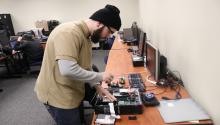 Gabrielle Ramos takes apart a computer as part of his IT training with Project WOW. Photo: Nigel Thompson/ALDÍA News