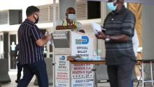 Poll workers help a voter put their mail-in ballot in an official Miami-Dade County ballot drop box on August 11, 2020 in Miami, Florida. (Photo by Joe Raedle/Getty Images)