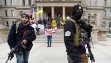 Protesters carrying rifles near the steps of the Michigan State Capitol building in Lansing Wednesday. The Washington Post