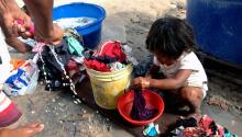 A girl of the Venezuelan Warao tribe washing clothes with her mother outside a shelter in Boa Vista, Brazil, on February 11, 2017. EFE/HRW/CESAR MUÑOZ ACEBES