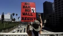 A May Day marcher makes fist while holding up a banner reading 'No Ban No Wall Resist' as they rally in the streets of downtown Los Angeles, California, USA, 01 May 2017. EPA/PAUL BUCK