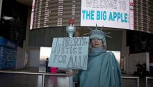 A woman dressed as the Statue of Liberty holds a placard 'Liberty and Justice for All' as she stands inside the arrivals section of Terminal 4 at John F. Kennedy International Airport in Queens, New York, USA, 04 February 2017. EPA/JOHN TAGGART