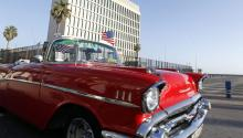 A file picture showing a classic car with the flag of the USA passing by the Office of US interests in Cuba, in Havana, Cuba, July 20, 2015. EPA/ERNESTO MASTRASCUSA