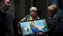 A victim advocate holds a painting of Mary and Jesus outside the Melbourne Magistrates Court in Melbourne, 26 July 2017. Cardinal Pell, 76, Australia's most senior Catholic, was charged on 29 June 2017, with multiple counts of historical sexual assault offences. EPA/JOE CASTRO