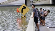 Spectators view the submerged highway interchange of Interstate 10 at Post Oak Road during a break in the rain in Houston, Texas, USA, 27 August 2017. EPA/MICHAEL WYKE
