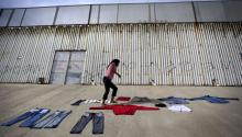Marta Sandoval, 36, lays out clothing to dry in front of the US-Mexico border wall on the bank of the Tijuana River canal, which has become home to hundreds of people deported from the US, in Tijuana, Mexico, 03 May 2013. EPA-EFE FILE/DAVID MAUNG