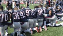 New England Patriots players hold hands and kneel during the National Anthem prior to the start of their game against the Houston Texans at Gillette Stadium in Foxboro, Massachusetts, USA, 24 September 2017. EPA-EFE/JOHN CETRINO