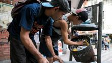 Two menrummaging through trash cans for something edible, in Caracas, Venezuela on Sept. 20, 2017. EPA-EFE/Miguel Gutierrez