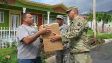 Officers of the National Guard of Puerto Rico deliver boxes with food to a inhabitant, in Jayuya, Puerto Rico, Oct. 11, 2017. EPA-EFE/JORGE MUÑIZ