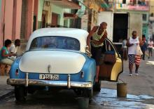 A man cleans an old US car in Havana, Cuba, on Dec. 17, 2017.