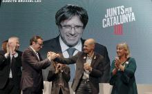 Junts per Catalunya's candidates Josep Rull (2ndL) and Xavier Quintillá (2ndR) shake hands as Catalonia's former president Carles Puigdemont (at the screen) speaks in a videoconference from Brussels during an electoral campaign event in Lleida, Catalonia, Spain, Dec. 18, 2017.