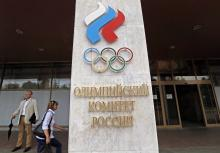People walk in front of the Russian Olympic Committee headquarters and Russian Athletics Federation office in Moscow, Russia, July 19, 2016.