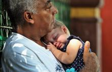 A man carries a baby in Havana, Cuba, Jun. 25, 2015.