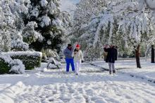 Residents walk in a park covered in snow in Monclova, Coahuila, Mexico, Dec. 8, 2017.