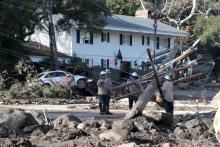 A handout photo made available by the Santa Barbara County Fire department shows Kerry Mann navigate the large boulders and mudflow that destroyed the home of her friend who has not been seen since the early hours of 09 January following heavy rains in Montecito, California, USA, 10 January 2018.