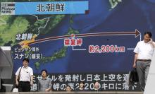 Pedestrians walk under a large-scale monitor displaying the flying course of a North Korean ballistic missile flying over Japan on a TV news broadcast in Tokyo, Japan, Sep. 15, 2017.