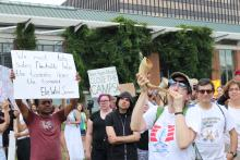 Cantor Naomi Hirsch blows the shofar, a Jewish instrument, as a call to action at the July 4th protest in Philadelphia.