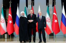 Turkish President Recep Tayyip Erdogan (C), Russian President Vladimir Putin (R) and Iranian President Hassan Rouhani (L) join hands as they pose for a family photo during their meeting at the Presidential Palace in Ankara, Turkey, Apr. 4,l 2018. EPA-EFE/MIKHAIL KLIMENTYEV/SPUTNIK/KREMLIN / POOL