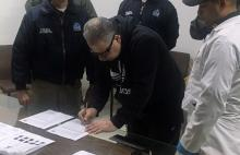 Former militia commander Daniel Rendon Herrera (C) signs documents as Interpol agents watch on April 23, 2018, in Bogota, Colombia. EPA-EFE/Colombian National Police