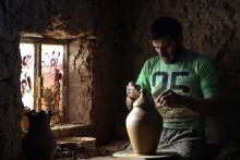 A potter works on a clay pot at a traditional pottery workshop in Armanaz, Idlib Governorate, Syria, Jul. 8, 2018. EPA-EFE/MOHAMMED BADRA