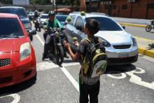A boy left all on his own juggles for money or food on Aug. 24, 2018, in Caracas, where the terrible economic crisis Venezuela is going through has caused thousands of children to be left behind by their parents who have left the country to find somewhere they can make a decent living. EFE-EPA/Cristian Hernandez