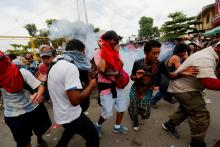 Honduran migrants clash with Guatemalan police on Oct. 28, 2018, in the border town of Tecun Uman before breaking through a metal fence at the border with Mexico and entering Mexican territory. EFE-EPA/ESTEBAN BIBA