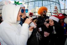 People eat grapes to the sound of twelve strokes at noon in front of the clock at Puerta del Sol square, downtown Madrid, Spain during the last 'rehearsal' of New Year's Eve tradition, Dec. 31, 2018. EFE