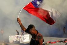 A demonstrator holds a Chilean flag during a protest. November 9. REUTERS/Pablo Sanhueza Taken from thestar.com