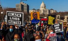 People hold signs during a 'Justice for George Floyd' march in Saint Paul, Minnesota, on 19 March. Photograph: Kerem Yucel/AFP/Getty Images