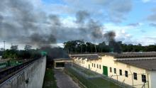 A column of smoke leaves a building after a violent clash between two rival factions in a penitentiary complex in Manaus, Brazil. At least sixty people were killed during a violent clash between two rival factions in a prison complex. Photo:EFE