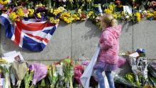A young girl looks at flowers in front of the Houses of Parliament near the scene of 22 March terror attack, in central London, Britain, 26 March 2017. A terror attack took place on 22 March in London leaving five people dead, including the attacker, and 31 people injured. EFE/EPA/HANNAH MCKAY