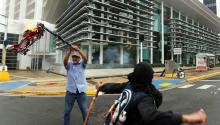 Un manifestante ondea una bandera quemada ,en San Juan, Puerto Rico, durante el paro general contra los recortes, que coincide con el Primero de Mayo, Día Internacional del Trabajador. EFE