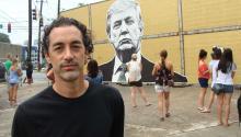 El artista estadounidense Joseph Guay posa junto a un muro que diseñó para crear conciencia sobre los problemas migratorios. EFE