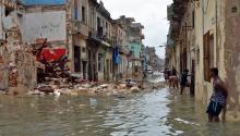 Foto tomada el 10 de septiembre de 2017, de habitantes que caminan por una calle inundada tras el paso del huracán Irma, en La Habana (Cuba). EFE