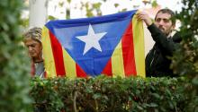 Several people hold a estelada, the Catalan independence flag, at the gates of the National Court, in Madrid. EFE / Mariscal