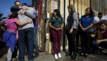 Un grupo de personas abrazan a sus familiares en una de las puertas de la valla fronteriza entre Estados Unidos y México,en Tijuana (México). La política antinmigración de Trump ha puesto las cosas difíciles a los indocumentados. Foto: EFE/David Maung
