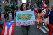 A woman displays a sign with the death toll for Hurricane Maria estimated by the recent Harvard study on June 10, 2018 at the annual Puerto Rican Day parade on Fifth Avenue in New York City. EFE