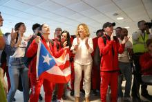 Puerto Rican women's basketball team captain Pamela Rosado dances with the Puerto Rican flag after returning home from Olympic qualifiers in France. The Puerto Rico women's basketball team qualified for its first Olympic games ever. Photo: Federación de Baloncesto de Puerto Rico (Facebook).