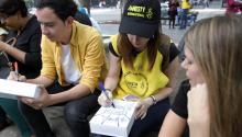 Activistas y público en general convocados porAmnistíaInternacionalescriben pensamientos en ladrillos simulados que forman un muro hoy, martes 20 de junio de 2017, en Ciudad de México (México).