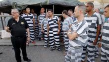 En esta foto de archivo del 23 de junio de 2012, los reclusos se reúnen junto al Sheriff del Condado de Maricopa, Joe Arpaio, mientras recorre el complejo de la cárcel de Tent City. (Matt York / AP)